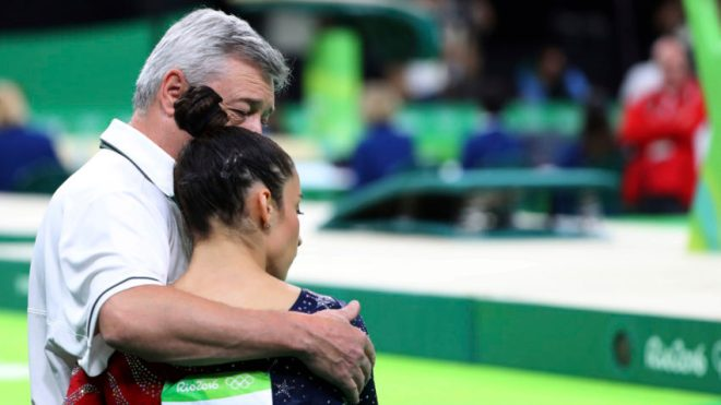 U.S. gymnast Alexandra Raisman with coach Mihai Brestyan after stumbling while competing in the balance beam during a women's team qualification round, at the Olympic Arena, Rio de Janeiro, Brazil, Aug. 7, 2016. (Chang W. Lee/The New York Times)