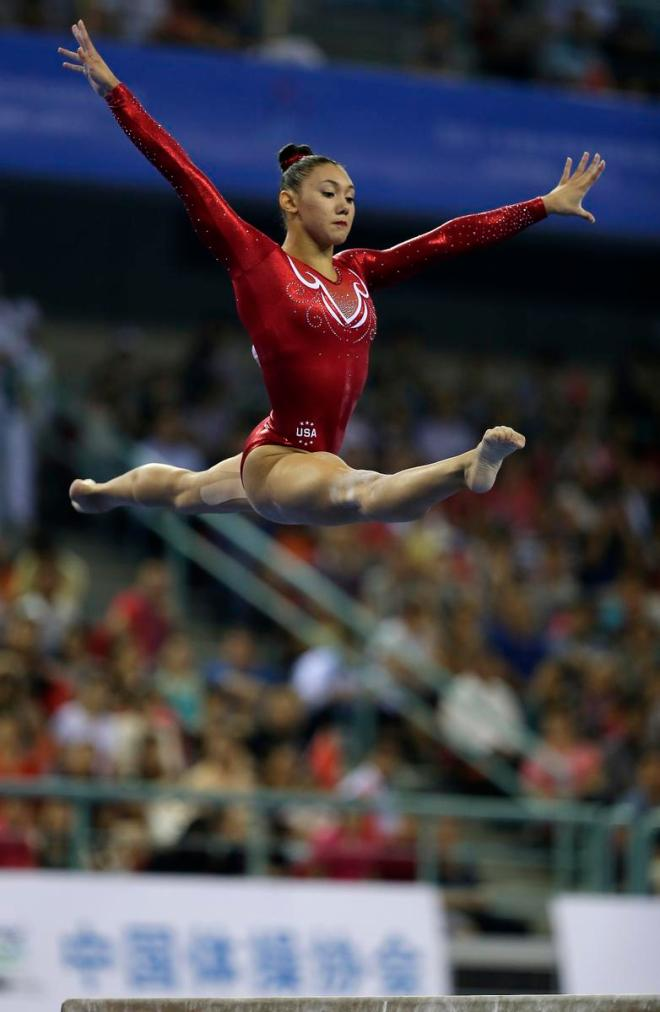 Kyla Ross of the United States jumps from the balance beam as she competes in the women's team final of the Artistic Gymnastics World Championship at the Guangxi Gymnasium in Nanning, capital of southwest China's Guangxi Zhuang Autonomous Region Wednesday, Oct. 8, 2014. (AP Photo/Andy Wong)